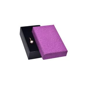 Černá krabička s fialovým třpytivým víčkem a černým polstrováním